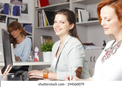 Young businesswoman working in graphic studio with colleagues. Small business.