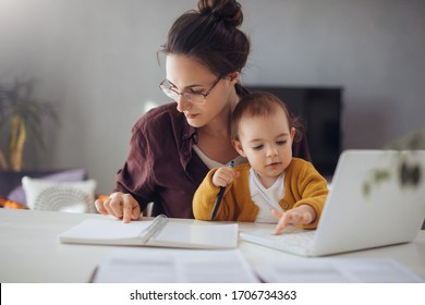 Young businesswoman working from home. Young mother working on lap top  at her home office. She working with her child.
