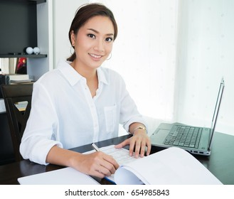 Young businesswoman working in office - Portrait of smiling beautiful Asian woman college student using laptop computer at home
