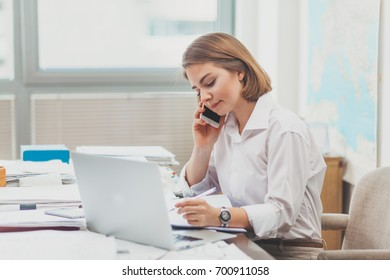 Young businesswoman working at the office and talking on the phone