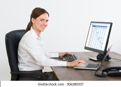 Young Businesswoman Working On Computer Showing Gantt Chart In Office