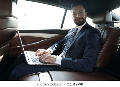 young businesswoman working on her laptop while sitting in the car