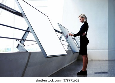 Young businesswoman working on interactive display while standing near another big computer monitor with blank copy space screen for your text message or content, elegant female selecting information