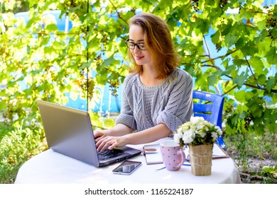 Young businesswoman working on a laptop at a work desk in nature. Modern concept of freelancing, work at home, digital nomad.