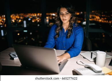 Young businesswoman working on a laptop at her office desk late into the night in front of windows overlooking the city
