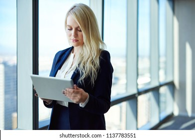 Young businesswoman working online with a digital tablet while standing by windows in a modern office
