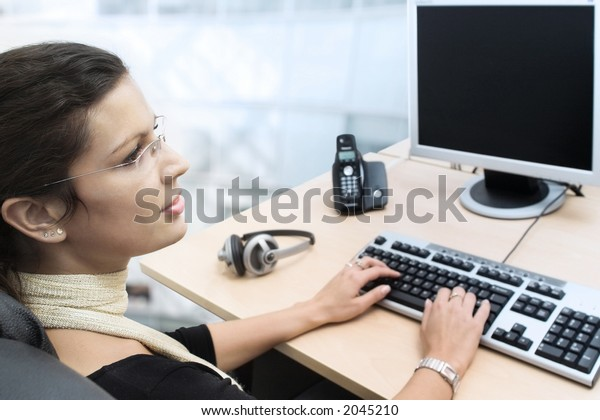 Young businesswoman works on a laptop computer in the modern office.
