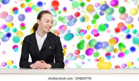 Young businesswoman with yellow rubber duck toy