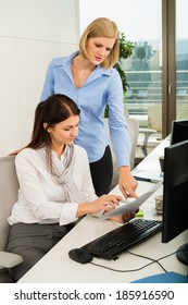 Young businesswomen discussing at office desk