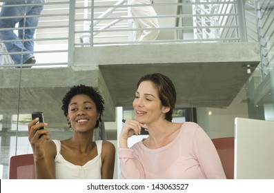 Young businesswomen reading text message on cell phone in office
