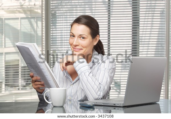 Young businesswomen reads a printed document.