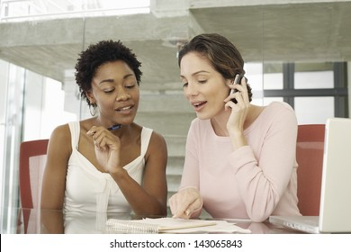Young businesswomen working together at table
