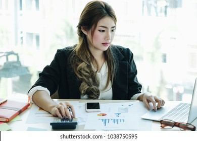 Young busy beautiful asian business woman working with calculator and laptop computer for financial accouting at office