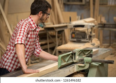 Young busy craftsman grinding timber using grinding machine. Professional woodworker standing in joiner's shop. Concept of craftsmanship, carpentry and handmade manufacturing.