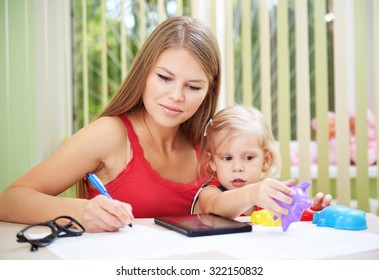 Young busy female telecommuting while her child is playing with toys. Pretty mom with cute daughter checking family bills and documents.