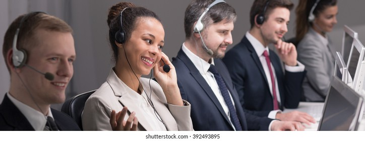 Young busy people working in call center corporation. Sitting by desks with computers and wearing headsets