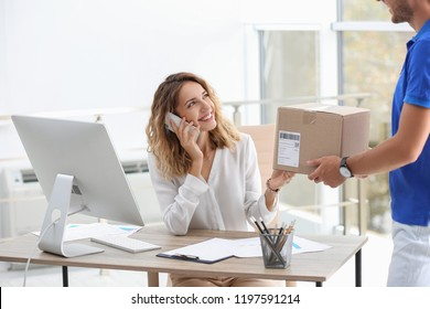 Young busy woman receiving parcel from courier in office