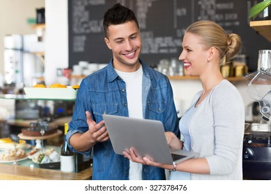 Young cafe owners looking at laptop