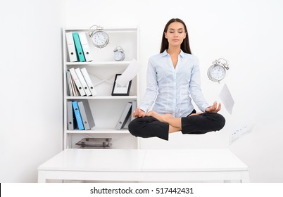 Young calm brunette business woman levitating above office desk and meditating in lotos position with flying objects around