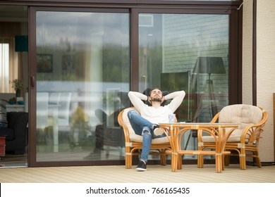 Young calm man relaxing sitting on terrace chair hands behind head, relaxed guy breathing fresh air, meditating with eyes closed outside modern house, resting alone, enjoying pleasant morning outdoor
