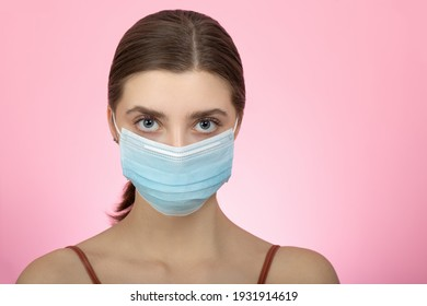 Young calm woman in blue medical mask on pink backgraund. Beauty during quarantine and isolation. - Shutterstock ID 1931914619