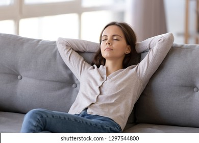 Young calm woman chilling relaxing leaning on comfortable sofa napping on couch in living room resting having healthy quiet nap, breathing fresh air, no stress free weekend at home, peace of mind