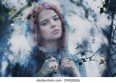 Young calm woman outdoors misty portrait through autumn leaves.
