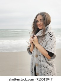 Young calm woman portrait against a sea, wniter skincare concept, oversize jersey, winter outdoor fashion
