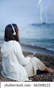 Young calm woman relax listening music under rain, sitting on a sea beach.