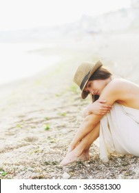 Young calm woman relax sitting on a sand sea beach dressed in white dress with open back and hipster hat, romantic foggy morning