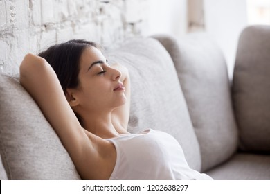 Young calm woman relaxing leaning back with hands behind head on comfortable sofa, having daydream, tired girl sleeping, napping on couch in living room, breathing calm, no stress free weekend at home