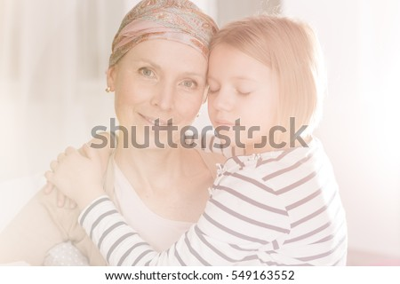Young cancer woman with headscarf having her family support