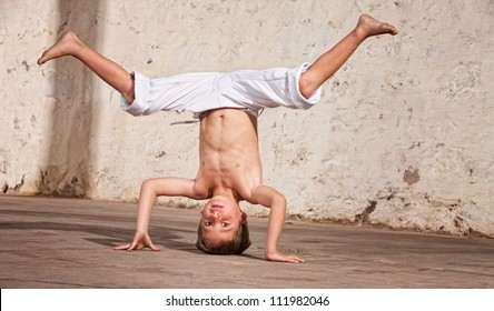 Young capoeria artist performing a headstand on concrete