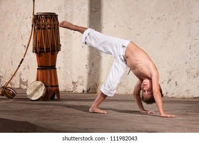 Young capoeria martial artist next to berimbau on floor