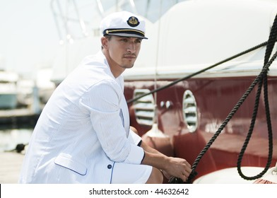 young captain looking away and holding rope of the yacht