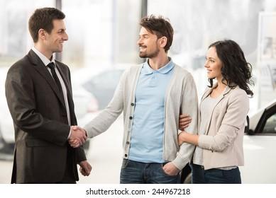 Young car salesman invites customers at showroom.