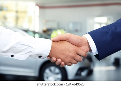 Young car salesman shaking hands with client in dealership, closeup