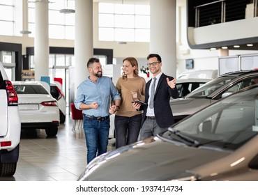 Junge Autoverkäufer, die Mitte des Alters ein neues Auto im Händlersalon vorstellen.