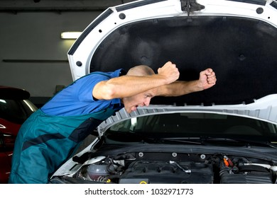 Young car service technician who repair the car engine motor.