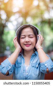 Young carefree attractive Asian woman enjoy to listening music in garden