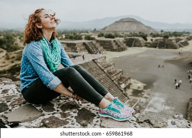Young carefree female tourist enjoying the pyramids of Teotihuacan in Mexico. Lifestyle portrait.