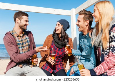 Young and carefree. Four happy friends talking to each other and smiling while sitting on the beach and drinking beer