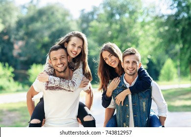 Young, carefree friends women and men in double date outdoors. Two happy caucasian couples having fun in summer park. Men piggyback smiling women. Love, romance, peoples relationship concept