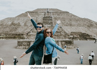 Young carefree and lovely couple of tourist enjoying the pyramids of Teotihuacan in Mexico. Lifestyle portrait.