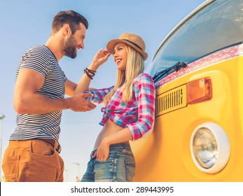 Young and carefree. Low angle view of beautiful young couple talking to each other and smiling while leaning at their retro minivan