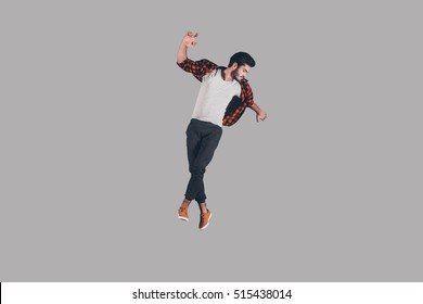 Young and carefree. Mid-air shot of handsome young man jumping and gesturing against background