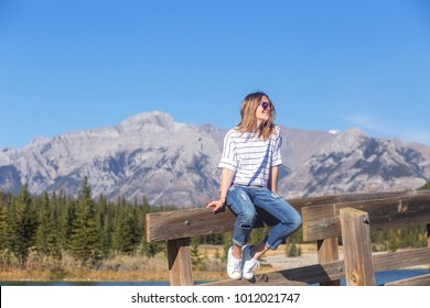 Young carefree smiling woman with windblown dark blond hair with highlights in casual outfit sitting on bridge rail looking away enjoying summer sunny windy day in Banff National Park, Alberta, Canada