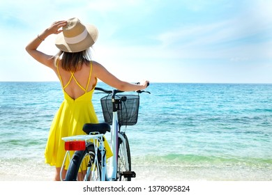Young carefree woman in bright yellow dress with bicycle at ocean beach. Unrecognizable female wearing broad brim straw hat biking on sandy sea shore on sunny day. Copy space, background.