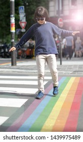 Young careful child balancing arms in crossing the street with fun, walking through the colorful rainbow lines and crosswalk of the city, halo effect, sunlight