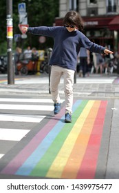 Young careful child crossing the street with fun, walking through the joyful colorful rainbow lines and crosswalk, city background, daylight